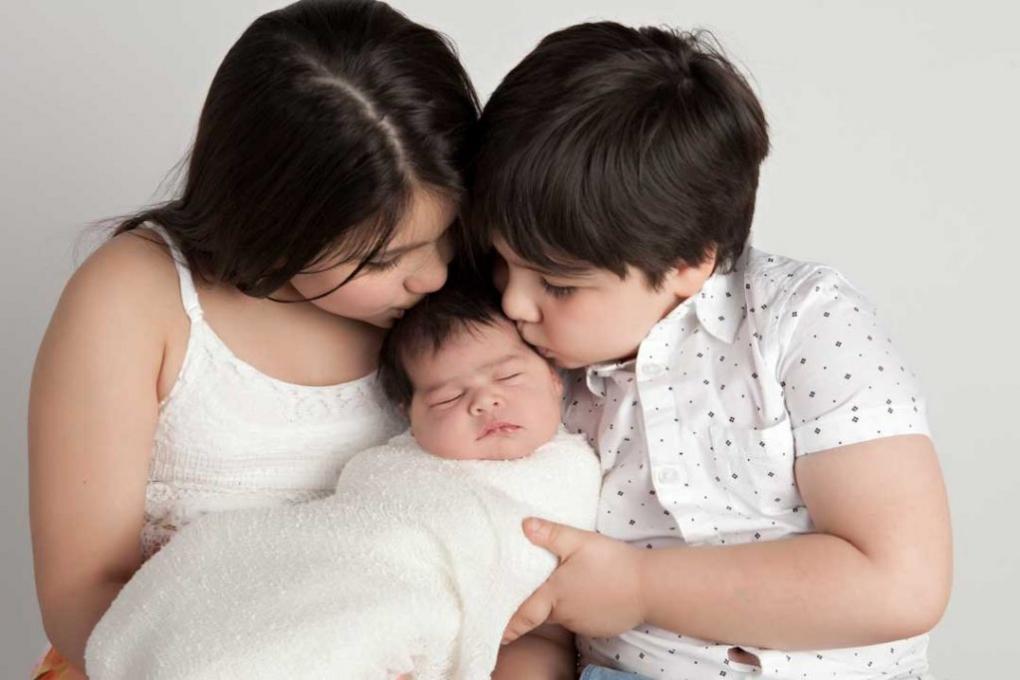 Siblings kissing newborn.