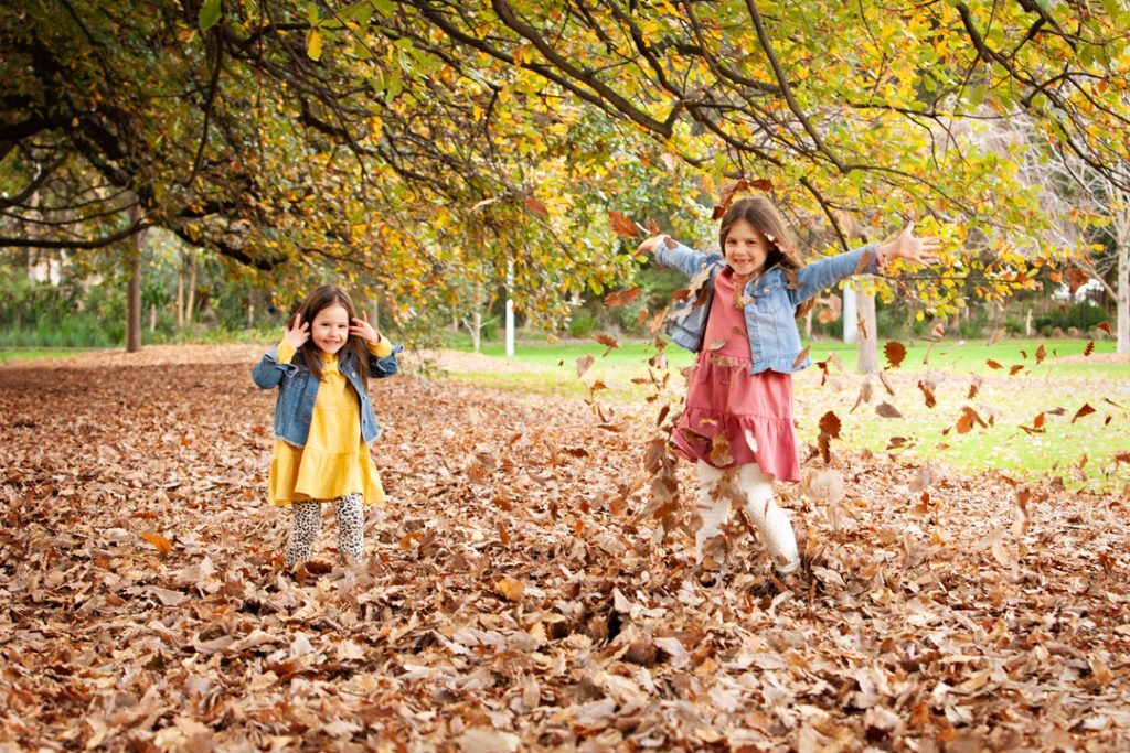 two girls playing in Autumn leaves